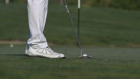 Мужской игрок в гольф кладя шар для игры в гольф внутри для того чтобы продырявить сток-видео