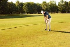 Мужской игрок в гольф кладя шар для игры в гольф на зеленый цвет стоковые фотографии rf