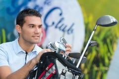 Мужской игрок в гольф выбирая клуб от сумки стоковые изображения