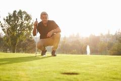 Мужской игрок в гольф выравнивая вверх удар, загоняющий мяч в лунку на зеленом цвете Стоковое Фото