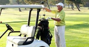Мужской игрок в гольф кладя гольф-клуб в сумку гольфа сток-видео