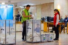 Мужской избиратель кладет избирательный бюллетень в урну для избирательных бюллетеней Рядом с контейнером его жена и ребенок Избр стоковое изображение