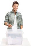 Мужской избиратель бросая голосование в урну для избирательных бюллетеней Стоковое фото RF