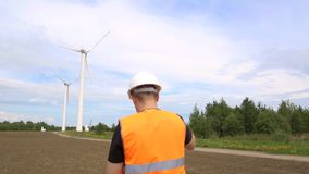 Мужской инженер выполняет осмотр и осмотр ветротурбины которая производит электричество путем вращать видеоматериал