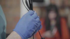 Мужской инженер в голубых перчатках свертывая спиралью кабель с черной пропиткой в мастерской на предпосылке женского коллеги : акции видеоматериалы