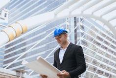 Мужской инженер по строительству и монтажу держащ светокопии читая детали работы над проектом стоковое фото
