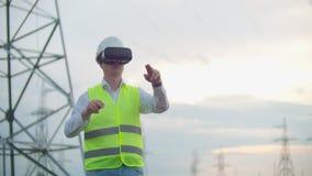 Мужской инженер управляет передачей альтернативной энергии от панелей солнечных батарей и ветровых электростанций к потребителям  акции видеоматериалы