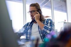Мужской исполнительный говорить на телефоне пока работающ на его столе стоковое фото