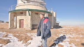 Мужской исследователь в джинсах и теплой форме на день зимы солнечный против фона научных зданий на a акции видеоматериалы