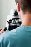 Мужской исследователь используя микроскоп в лаборатории стоковое изображение