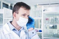 Мужской исследователь используя мобильный телефон на его рабочем месте в лаборатории стоковые изображения