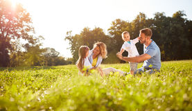 Мужской и женский играть с детьми снаружи стоковое изображение rf