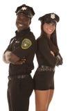 Мужской и женский полисмен спина к спине усмехаясь Стоковая Фотография RF