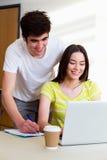 Мужской и женский студент колледжа используя компьтер-книжку в классе стоковые фото
