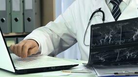 Мужской кардиолог смотря рентгеновский снимок кровеносных сосудов, печатая диагноз на компьтер-книжке акции видеоматериалы