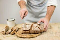 Мужской кашевар режет хлеб Стоковые Изображения RF