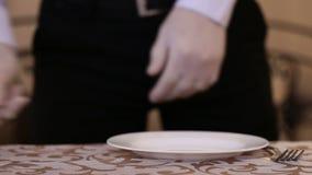 Мужской кельнер аранжирует комплект столового прибора на таблице в ресторане сток-видео