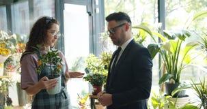 Мужской клиент говоря с усмехаясь флористом обсуждая экзотический завод в цветочном магазине акции видеоматериалы