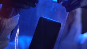 Мужской контролер кладет smartphone жертвы с уголовными отпечатками пальцев в полиэтиленовый пакет сток-видео
