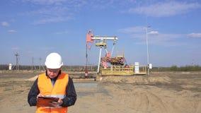 Мужской контролер-оператор в жилете сигнала и белом шлеме записывает чтения о масле блока насоса, газе и сток-видео