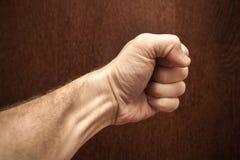 Мужской кулак над стеной темного коричневого цвета деревянной стоковое фото