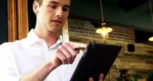 Мужской клиент используя цифровую таблетку в café видеоматериал