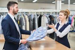 Мужской клиент принимает работнику прачечной женщины чистые одежды стоковая фотография