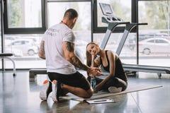 мужской личный тренер объясняя говорить с молодой атлетической женщиной стоковые фотографии rf