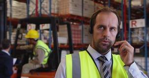 Мужской менеджер склада используя шлемофон и планшет 4k сток-видео