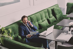 Мужской менеджер говоря smartphone в кафе Стоковые Изображения RF