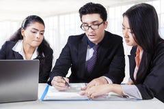 Мужской менеджер читая документ с партнерами Стоковые Фотографии RF