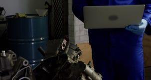 Мужской механик используя ноутбук пока ремонтирующ двигатель мотоцикла в гараже 4k видеоматериал