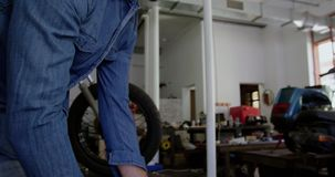 Мужской механик нажимая мотоцикл катит в гараж 4k ремонта акции видеоматериалы