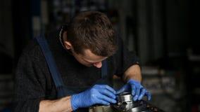 Мужской механик собирает отстраиванный заново мотор для автомобиля видеоматериал