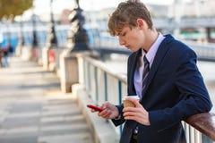 Мужской молодой взрослый подросток используя кофе сотового телефона выпивая стоковые фото