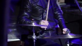 Мужской музыкант в черных одеждах активно играет барабанчики на этапе с голубым светом видеоматериал