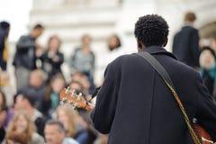 Мужской музыкант играя в улице около Sacre Coeur для денег Стоковая Фотография