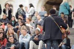 Мужской музыкант играя в улице около Sacre Coeur для денег Стоковые Изображения RF