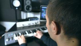 Мужской музыкант играя на синтезаторе на ядровой студии звукозаписи Запев игр человека музыки Пальцы пианиста на рояле видеоматериал