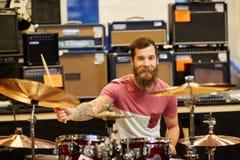 Мужской музыкант играя цимбалы на магазине музыки Стоковое фото RF