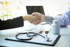 Мужской доктор в белом пальто тряся руку к женскому пациенту после s стоковые изображения