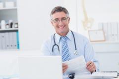 Мужской доктор держа документ на таблице Стоковые Фотографии RF