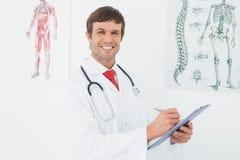Мужской доктор держа доску сзажимом для бумаги в медицинском офисе Стоковые Фото