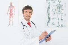 Мужской доктор держа доску сзажимом для бумаги в медицинском офисе Стоковая Фотография