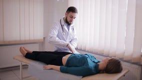 Мужской доктор делает пальпацию из брюшка пациента Девушка лежит на кресле в офисе ` s доктора видеоматериал