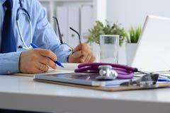 Мужской доктор используя компьтер-книжку, сидя на его столе Стоковые Фотографии RF
