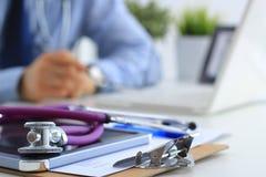 Мужской доктор используя компьтер-книжку, сидя на его столе Стоковое фото RF