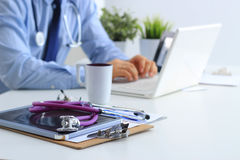 Мужской доктор используя компьтер-книжку, сидя на его столе Стоковые Изображения RF