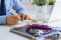 Мужской доктор используя компьтер-книжку, сидя на его столе Стоковое Изображение
