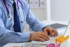 Мужской доктор используя компьтер-книжку, сидя на его столе Стоковое Изображение RF